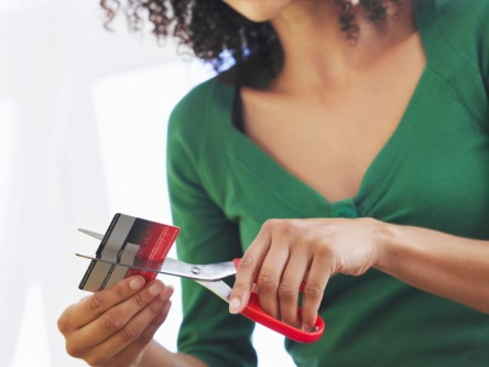 Midsection Of Woman Cutting Credit Card