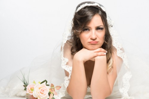 Sad and disappointed bride lying on the floor with rose flower