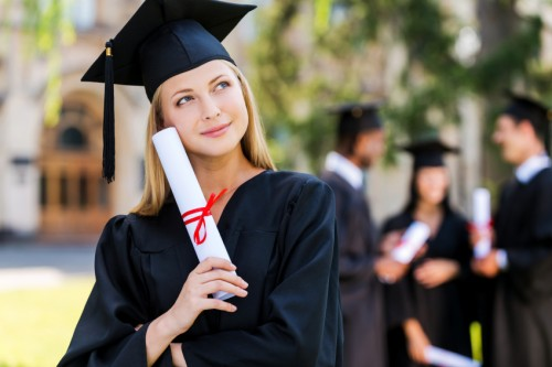 Dreaming of a bright future. Thoughtful young woman in graduation gowns holding diploma and looking away while her friends standing in the background