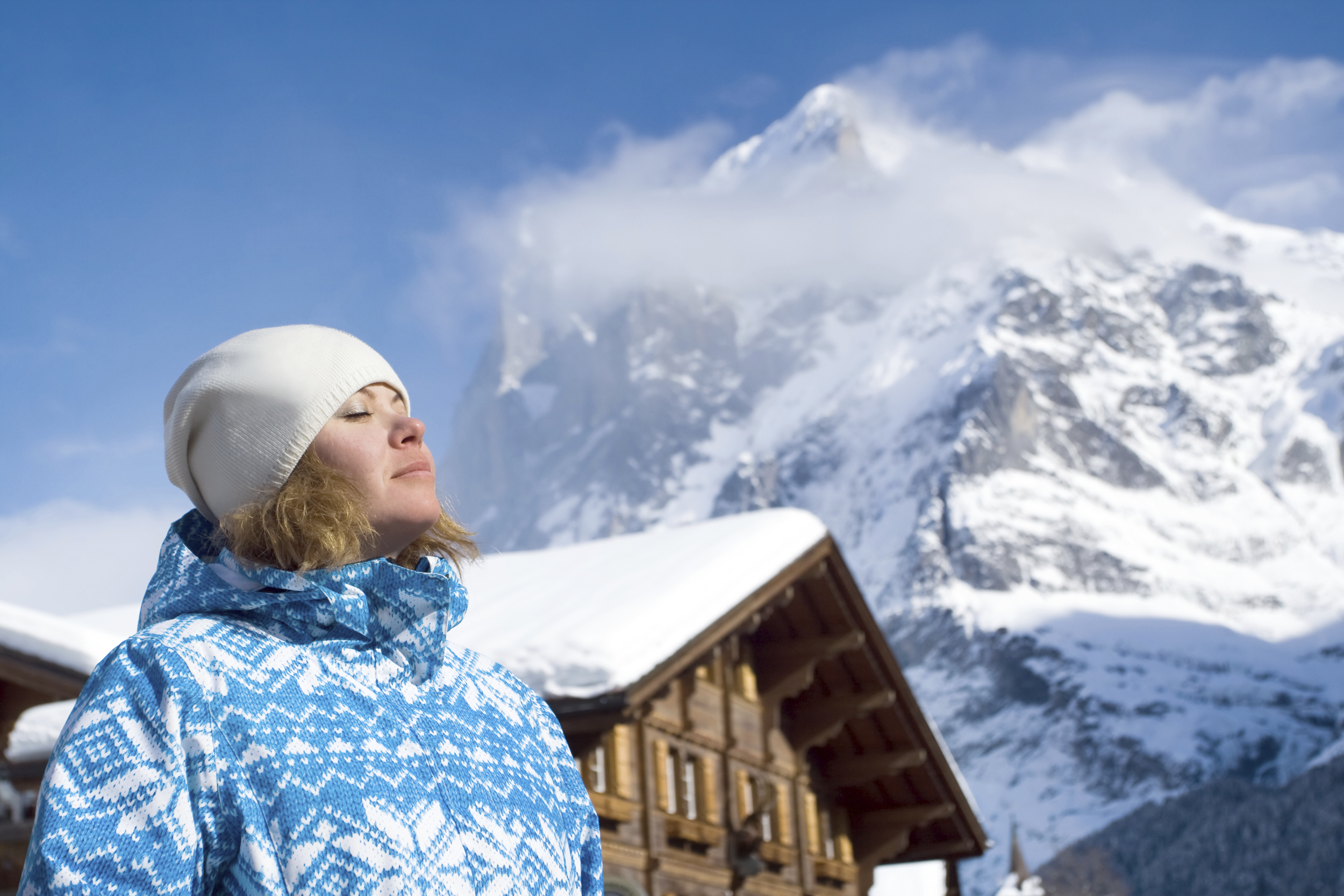 Beautiful young woman looking up. There are a top of alpine mountain summit on the background and a house(hotel). Winter, Switzerland.
