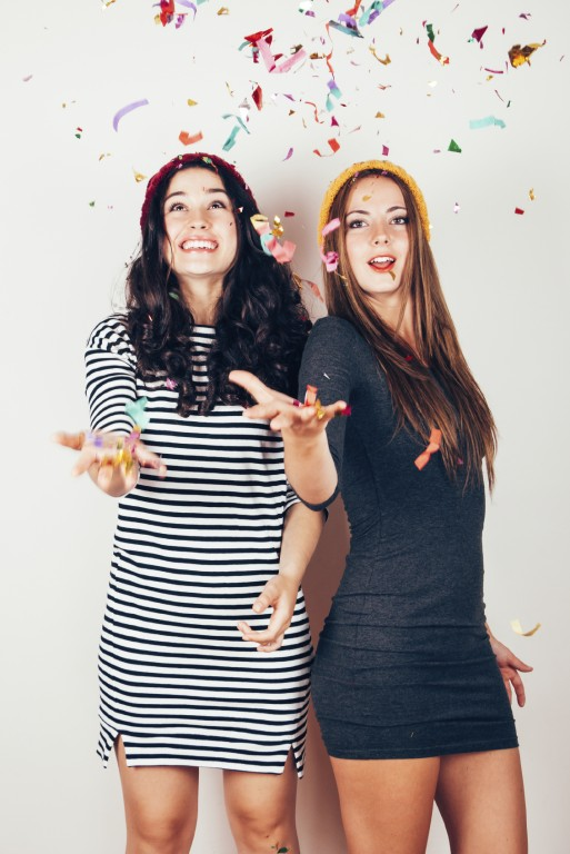 Party girls throwing confetti