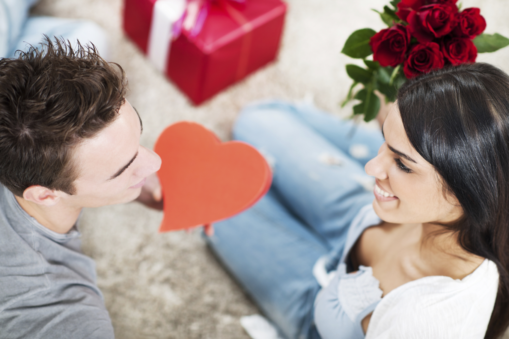 Couple sitting on the floor with presents for Valentines Day.