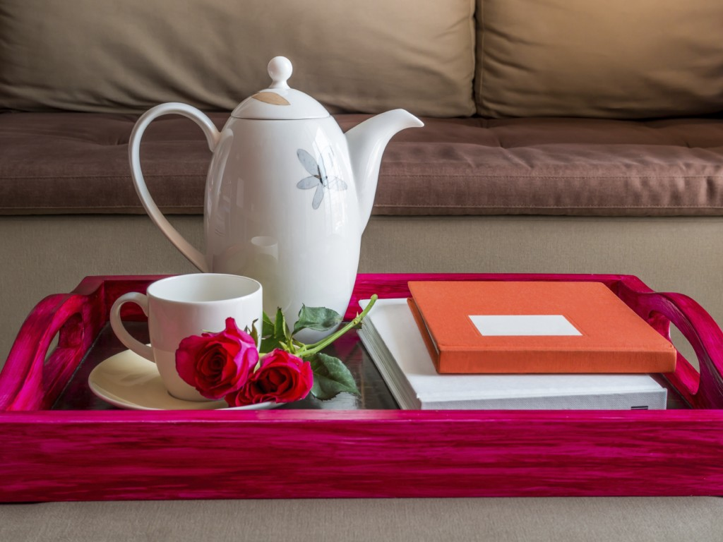 Cup of coffee with red roses in living room