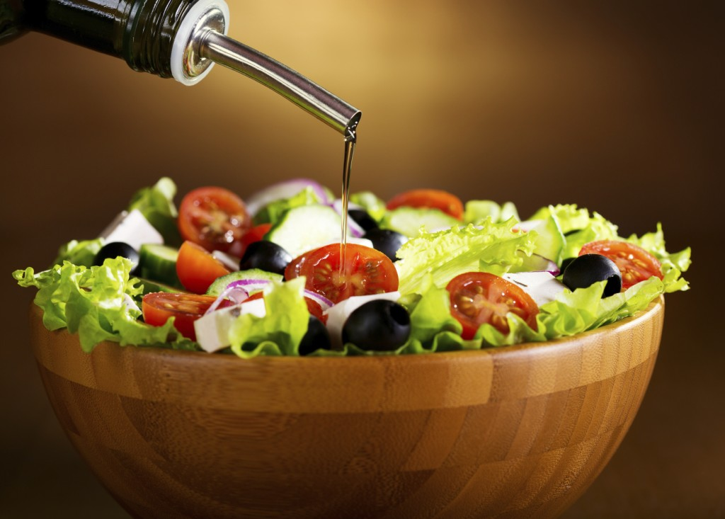 oil pouring into bowl of vegetable salad