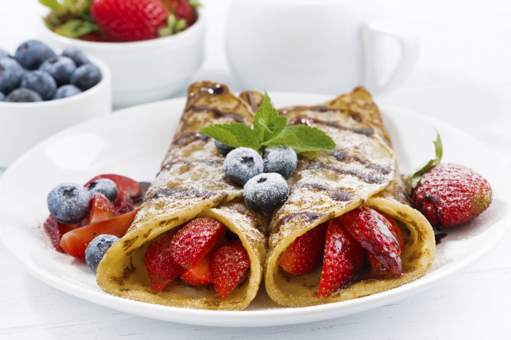 crepes with berries and chocolate sauce for breakfast on plate,