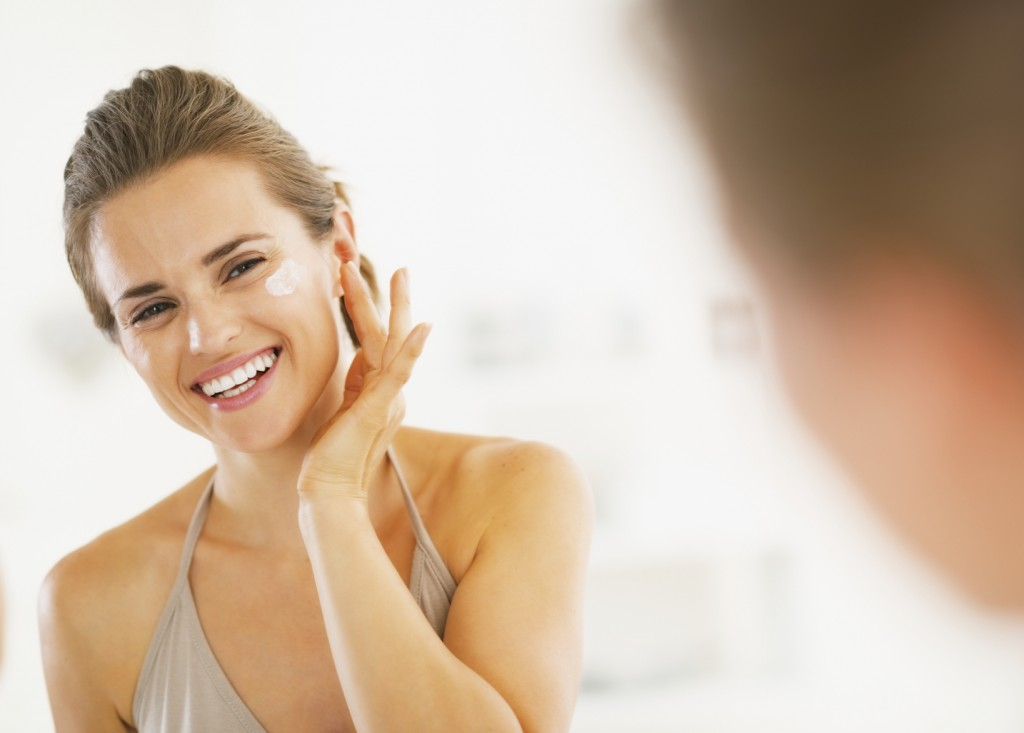 Smiling woman applying lotion to her face in a mirror