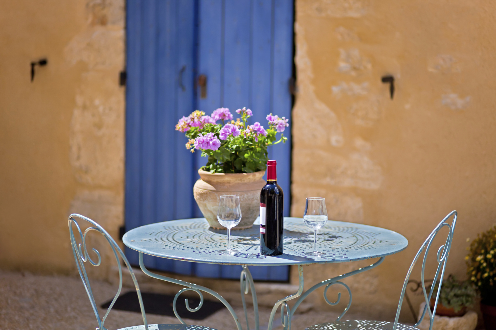 Table for two set with red wine. Provence, France.