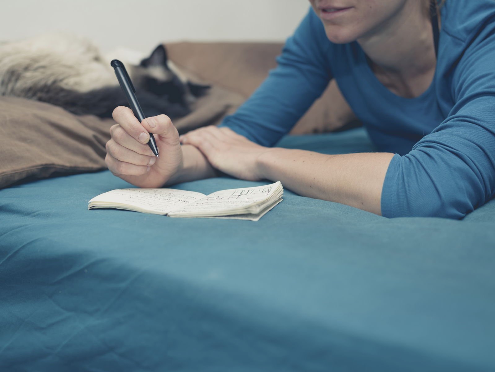 Woman taking notes in bed with cat