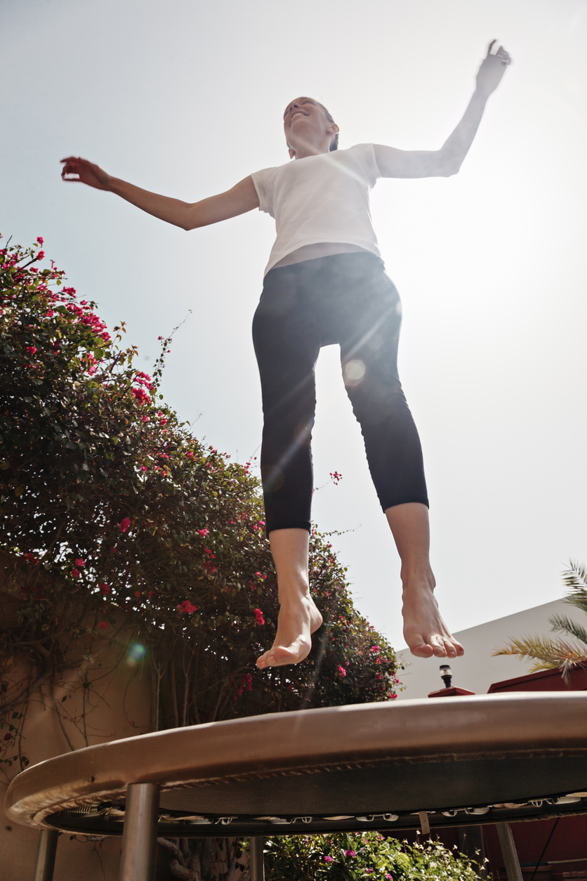 Young Female Jumping On Trampoline Outdoors